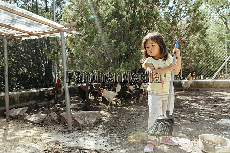 girl sweeping chicken farm with broom