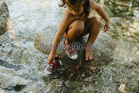 cute girl playing in flowing water