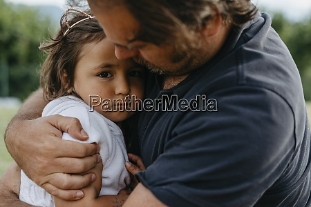 father embracing daughter while sitting at