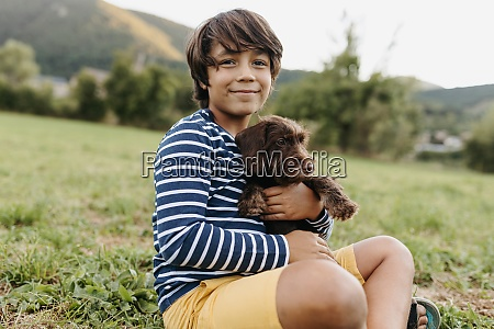 boy holding puppy while sitting on