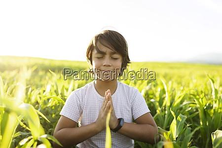 smiling boy practicing yoga while sitting