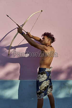 barechested young man with bow and
