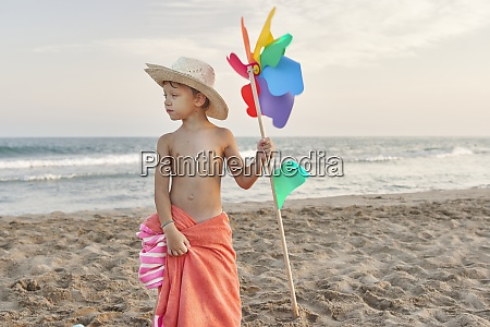 boy wearing hat holding windmill toy