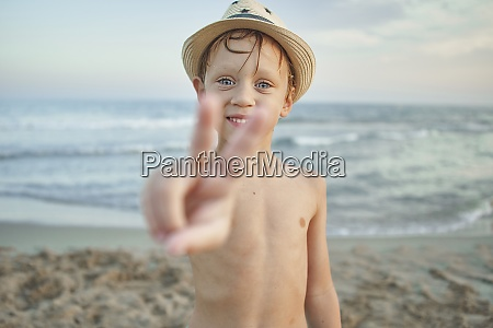 smiling boy showing peace gesture while
