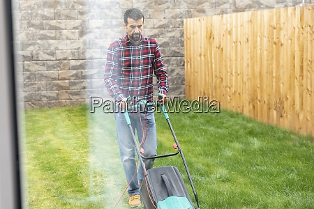 man walking with lawn mower while