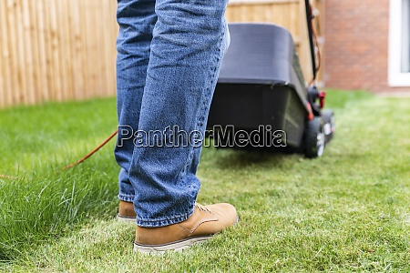 man standing with lawn mower at