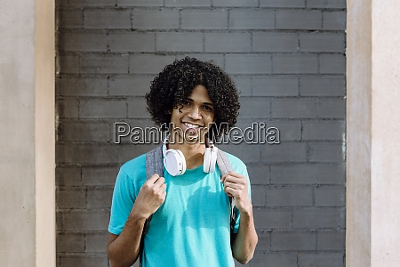 young man standing with headphone against