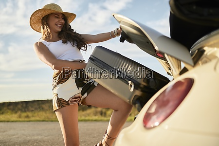 smiling young woman removing suitcase from