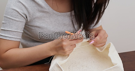 woman is crocheting with thread at