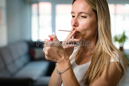 mid aged woman lighting a cigarette
