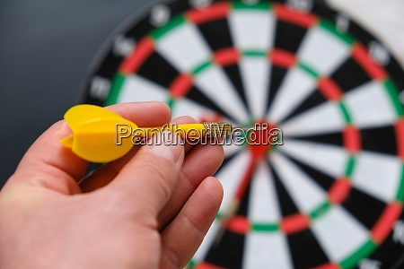 a hand throws darts on a