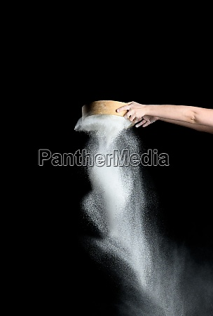 female hand sifts white wheat flour