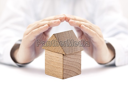 small wooden house protected by hands