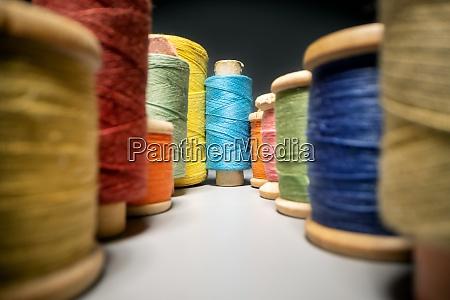 between colorful sewing thread spools closeup