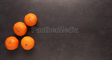 fresh clementines on a black stone