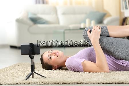 woman doing yoga exercises watching video