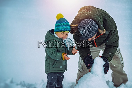 happy father with son making snowman