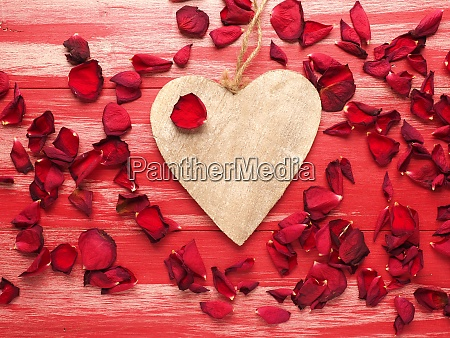 rustic wooden heart with rose petals