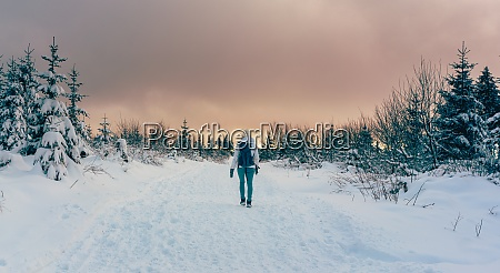 woman hiking through winter landscape during