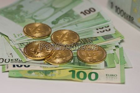 five golden bitcoins lying on many