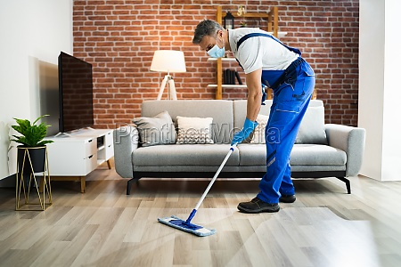 man cleaning the hardwood floor with