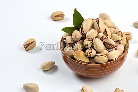 pistachio in bowl on white background