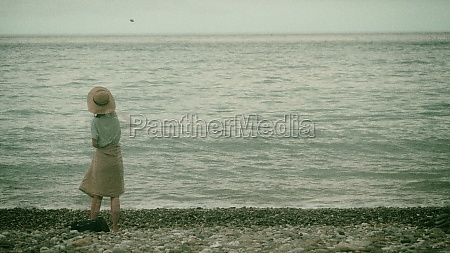 girl throwing stones at the beach