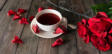 cup of tea with red roses