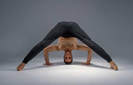 male yoga stands on his head