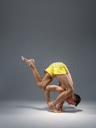 male yoga in a difficult pose