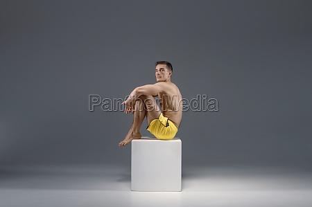 male yoga sitting on the pedestal