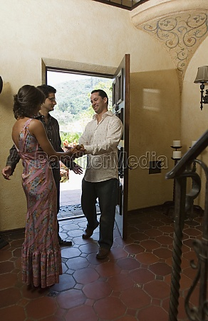 couple greeting guest at door