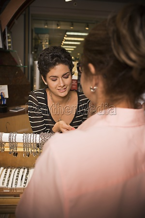 young woman helping customer in jewelry