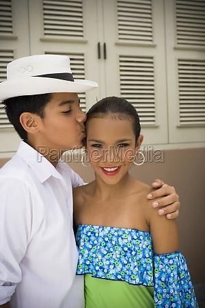 children wearing plena traditional attire kissing