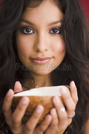 young woman holding coconut