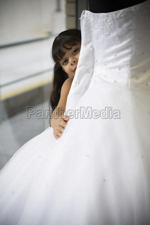 young girl looks peeks out from