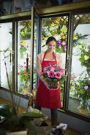 flower shop owner holding arrangement