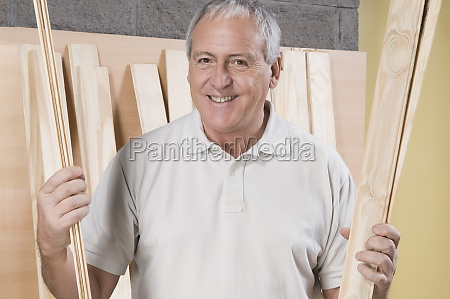 man holding wooden planks