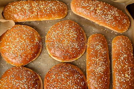 baked sesame buns on brown parchment