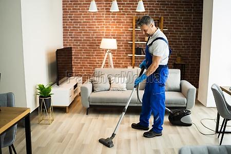 man in uniform vacuuming house floor