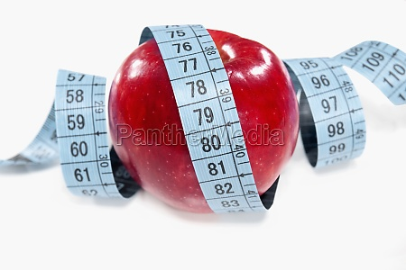 apple wrapped in a tape measure