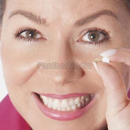 woman holding a pill and smiling