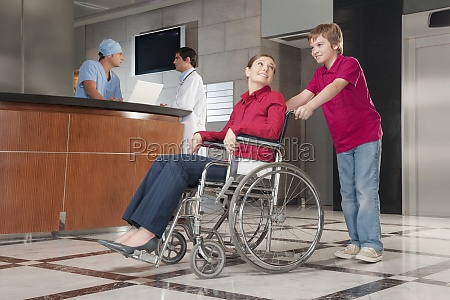 woman sitting in a wheelchair being
