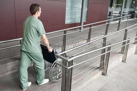 male nurse carrying a wheelchair