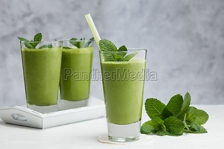 freshly blended green fruit smoothie in