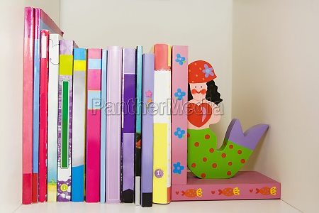 closeup of books and toy mermaids