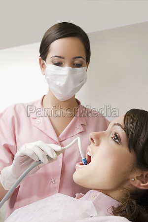 dentist cleaning womanZs teeth