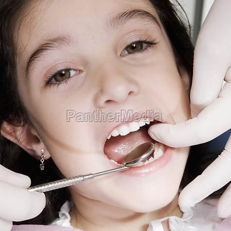 dentist checking girlZs teeth