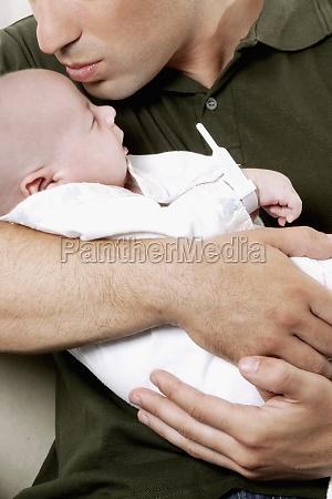 man pampering his newborn baby