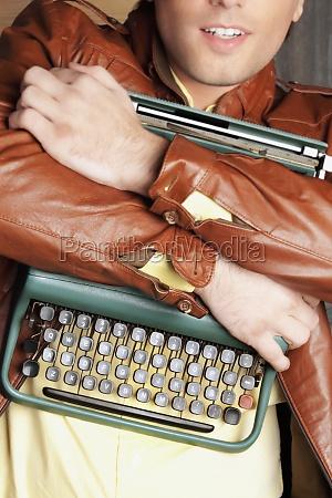 man carrying a typewriter